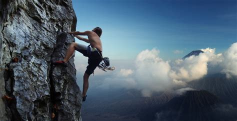 Young man climbing natural rocky wall with volcanoes on