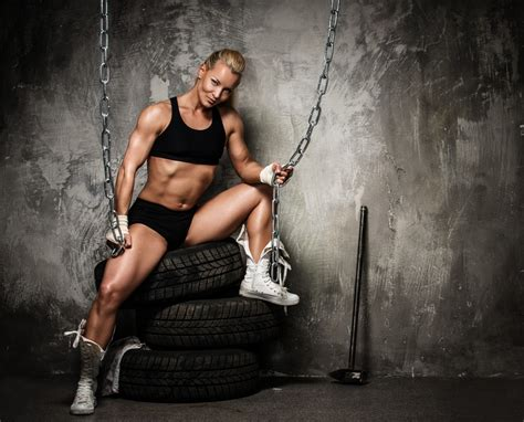 Beautiful muscular bodybuilder woman sitting on tyres and